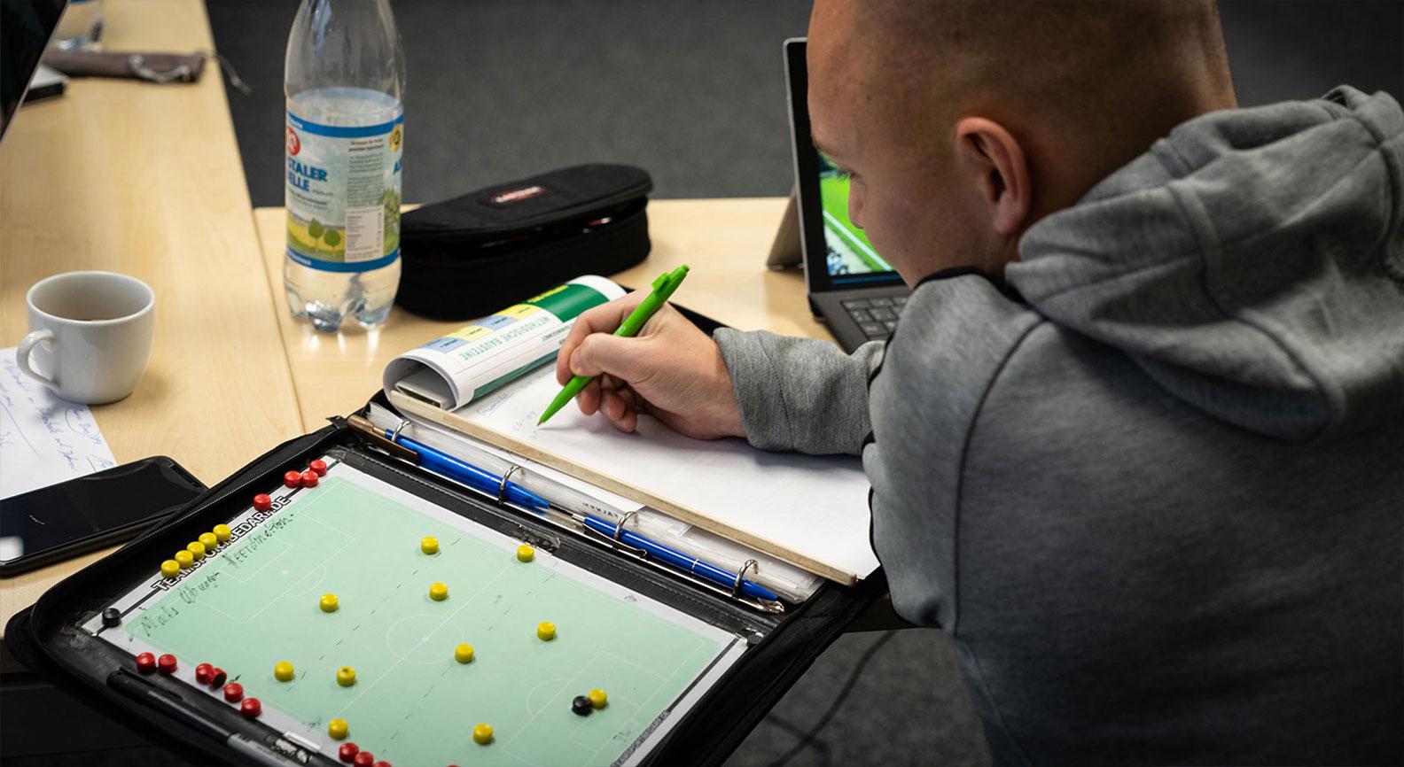 Mann analysiert Fussballspiel