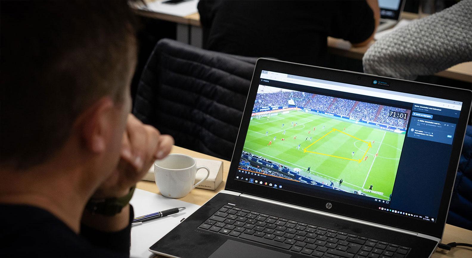 Mann analysiert Fussballspiel auf Laptop
