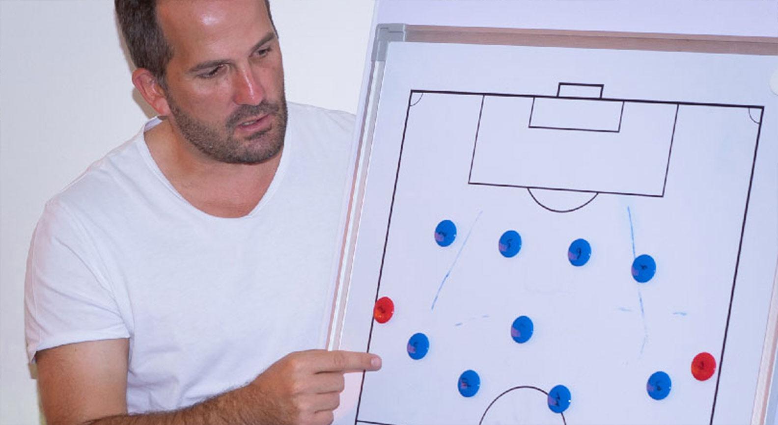 Mann analysiert Spielplan auf Tafel
