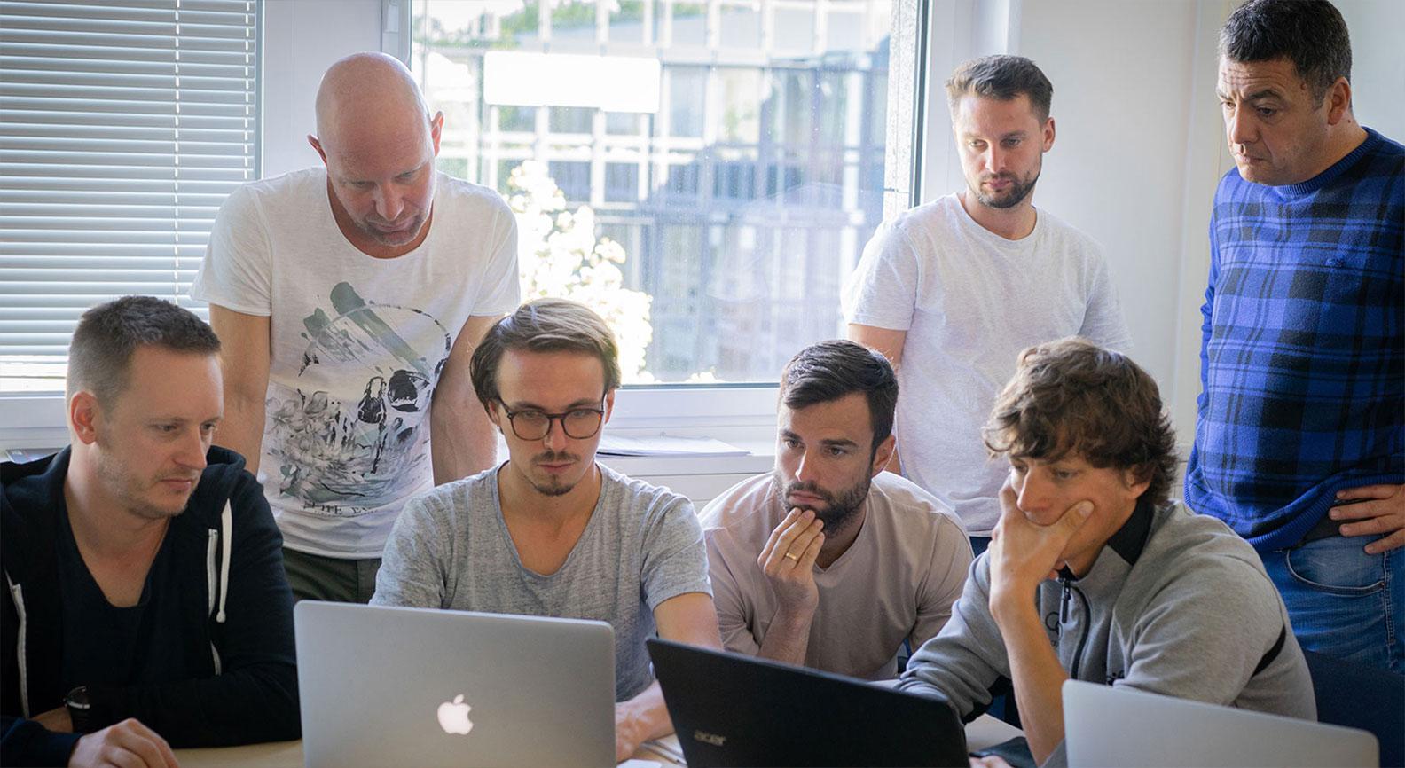Männer sitzen vor Laptops